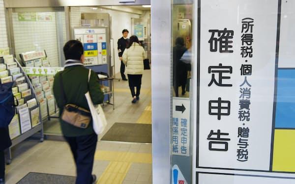 確定申告が始まり、手続きのため税務署に入る人たち(18日、東京都港区)