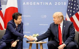 トランプ米大統領(右)と握手する安倍首相(2018年11月30日、ブエノスアイレス)=代表撮影・共同