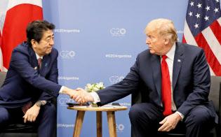 トランプ米大統領(右)と握手する安倍首相(昨年11月のG20)=共同