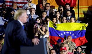 18日、ベネズエラ国旗を掲げる聴衆を前に演説するトランプ大統領(左)=ロイター