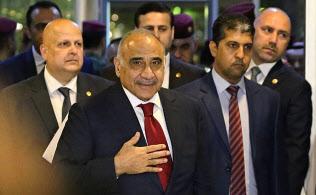 アブドルマハディ首相(中央)はテクノクラートの印象が強いが、政治基盤は弱い=AP