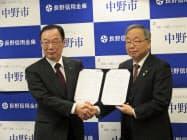 連携協定を結び握手を交わす市川理事長(左)と池田市長
