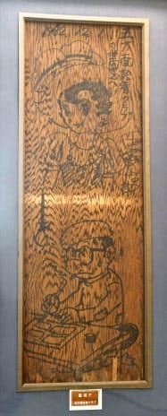トキワ荘解体時に取り外され、手塚治虫さんが若手記者に贈った天井板。「リボンの騎士」のキャラクターと、自身の姿が描かれている=共同
