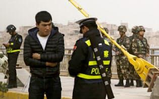 新疆ウイグル自治区のカシュガルで住民のIDカードをチェックする警察官=ロイター