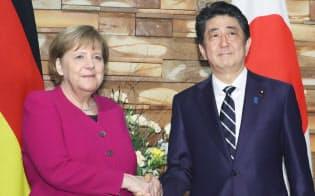 会談を前にドイツのメルケル首相(左)と握手する安倍首相(2月4日、首相官邸)