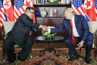 2018年6月12日、会談で握手する北朝鮮の金正恩朝鮮労働党委員長(左)とトランプ米大統領=シンガポール(AP=共同)