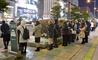 札幌市中心部でタクシー乗り場に列を作る人たち(21日午後10時24分)=共同