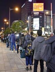 札幌市中心部でタクシーを待ち、列を作る人たち(21日午後10時23分)=共同