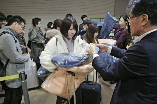 地震の影響で新千歳空港に足止めされ、配られた毛布や水を受け取る利用客ら(22日未明)=共同