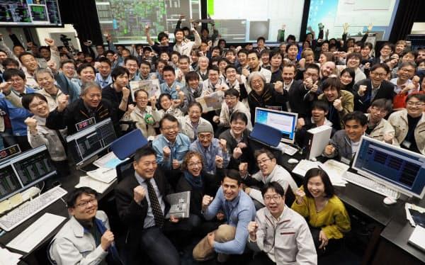 探査機「はやぶさ2」の着陸を祝い、管制室で記念撮影するJAXAの関係者ら(22日午前、神奈川県相模原市)=JAXA提供