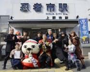 愛称「忍者市駅」の表示と写真に納まる三重県伊賀市の岡本栄市長(中)ら(22日午前)=共同