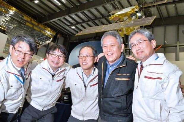 着陸をなし遂げ、はやぶさ2の模型を背に記念撮影するJAXAの津田雄一プロジェクトマネージャ(中)ら(2月22日、相模原市)=笹津敏暉撮影