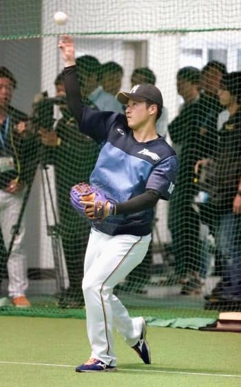 室内練習場でキャッチボールする日本ハム・吉田輝(22日、国頭)=共同