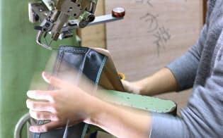 大型のミシンで木枠に革を縫い付ける