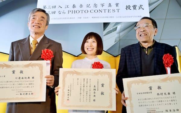 第三回「入江泰吉記念写真賞」を受賞した真鍋奈央さん(中)ら(22日、奈良市)
