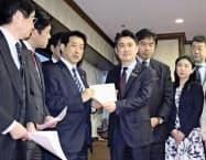 塩崎元厚労相(左から3人目)から、懲戒権の在り方の検討を求める決議を受け取る山下法相(同4人目)=19日午後、法務省