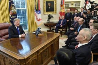 22日、米ホワイトハウスの大統領執務室で面談するトランプ大統領(左)と中国の劉鶴副首相(手前の左から2人目)ら=AP