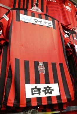 背中にくまモンのイラストが入ったサッカーJ3のロアッソ熊本の昨季のユニホーム(熊本市内のスポーツ用品店)=共同