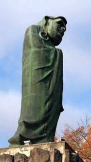 飛騨市神岡町の「立ち達磨」の銅像は遠く離れた米ニューヨークの自由の女神像の背中を見つめる