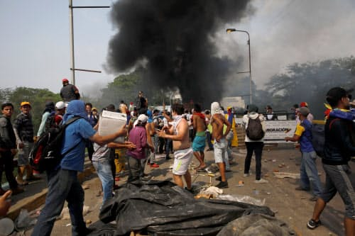 23日、支援物資の搬入を巡りベネズエラ国民とベネズエラ軍が衝突した(コロンビア北部ククタ)=ロイター