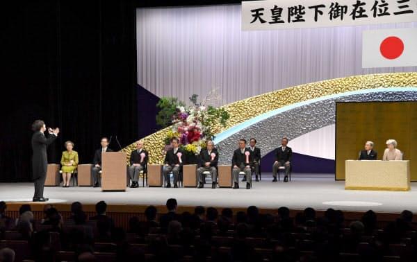 天皇陛下の在位30年記念式典で、「歌声の響」を披露する三浦大知さん(左)(24日午後、東京都千代田区の国立劇場)=代表撮影