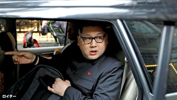 25日、警察に付き添われ車でホテルを離れる金正恩氏のそっくりさんの男性(ハノイ)=ロイター