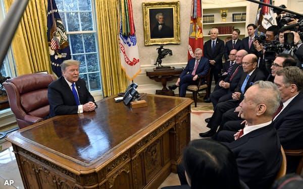 中国のインターネット上では、トランプ米大統領の執務机の前に座らされた劉鶴・中国副首相(手前右)の姿が、清の政治家、李鴻章と比べられている(2月22日)=AP