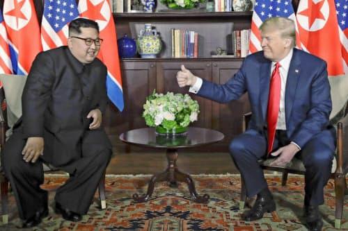昨年6月の初会談で談笑する米朝首脳(シンガポール)=AP