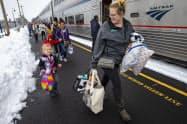 26日、米オレゴン州で列車から降りる乗客=AP
