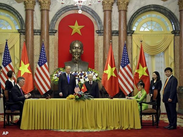 署名式に臨むグエン・フー・チョン共産党書記長(中央右)とトランプ大統領ら=AP