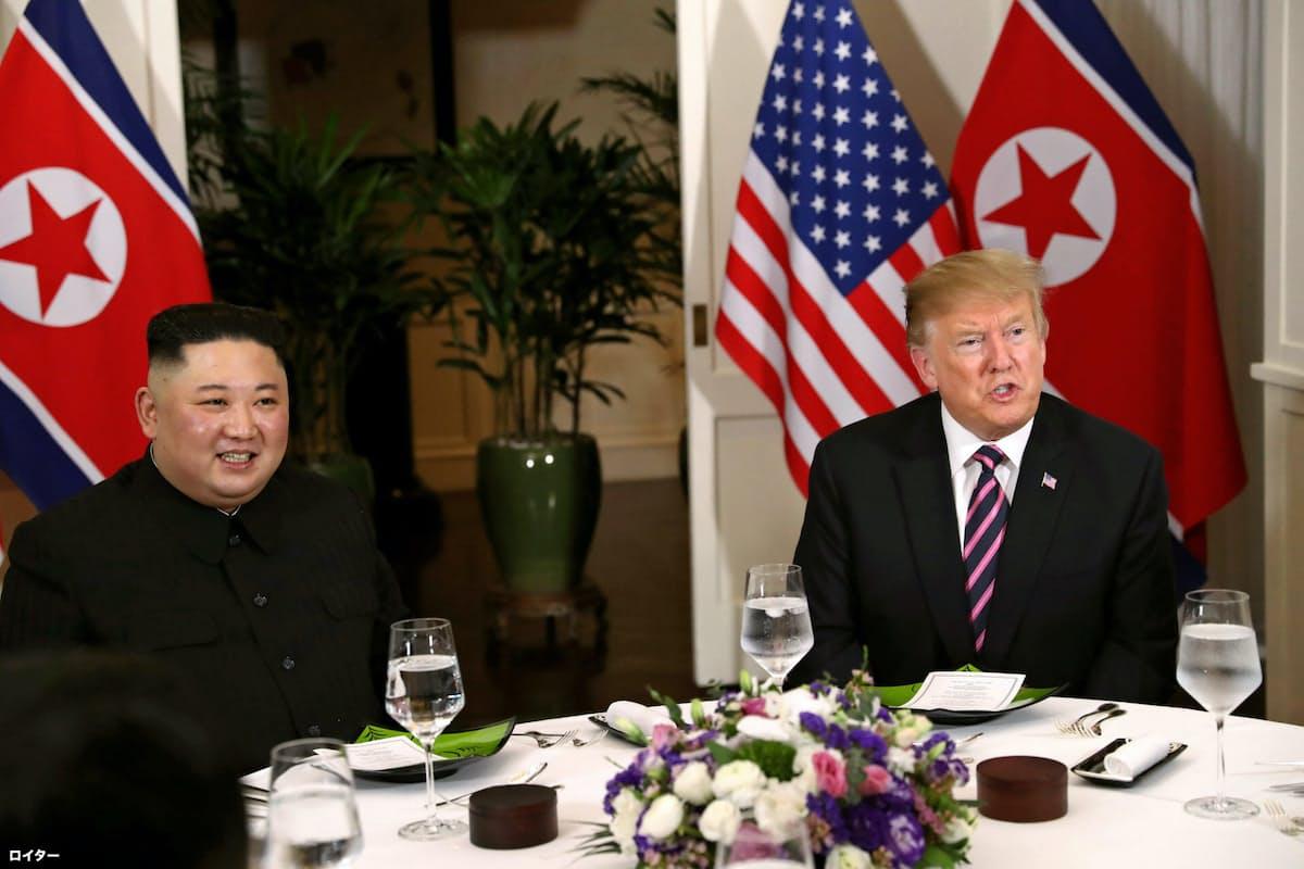 夕食をともにするトランプ大統領(右)と金正恩氏=ロイター