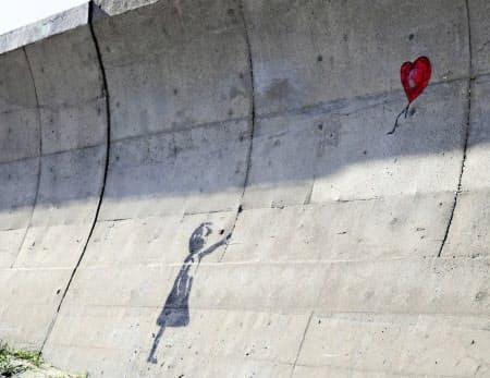 千葉県九十九里町の漁港の防波護岸に描かれたバンクシーの作品「少女と風船」に似た絵(同町提供)=共同