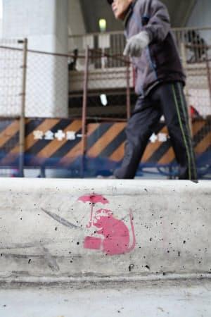 阪神電車の高架下にある縁石で、傘とかばんを持ったネズミのような絵がみつかった(2月下旬、兵庫県西宮市)