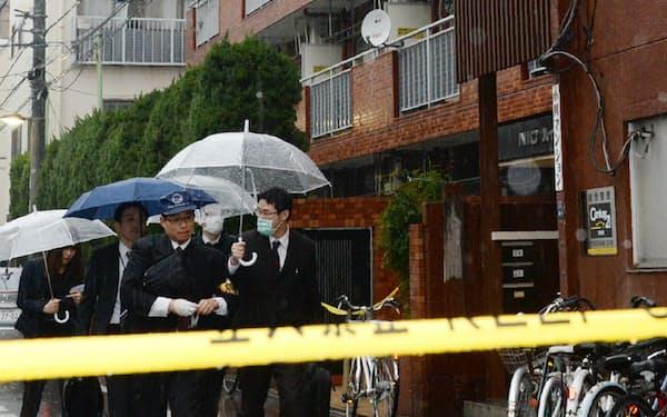 女性の遺体が見つかったマンション周辺を調べる警視庁の捜査員(28日、東京都江東区)