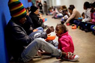 収容施設で子供に食事を与える中米移民(メキシコ北部・シウダフアレス)=ロイター