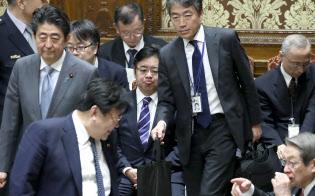 安倍首相の答弁書が入ったトートバッグを手に衆院予算委に臨む秘書官