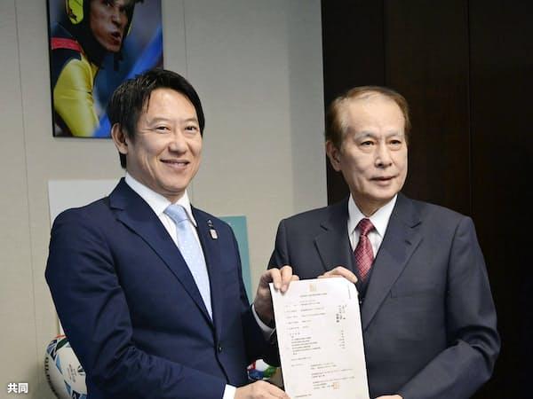 スポーツ庁の鈴木大地長官(左)にUNIVAS設立を報告する鎌田薫会長(1日午前、スポーツ庁)=共同
