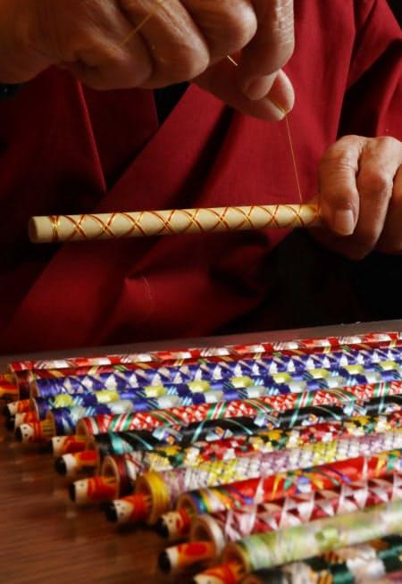 絹糸を筆軸にきつく巻き付け、色鮮やかな模様を生み出す
