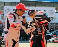 ホンダの八郷社長(左)からヘルメットをプレゼントされるトヨタ自動車の豊田社長(右)(2日、三重県鈴鹿市)