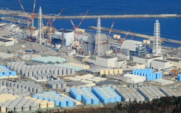 廃炉作業が続く福島第1原発の(左奥から)1号機、2号機、3号機、4号機。手前は汚染処理水などが入ったタンク群(1日、福島県大熊町)