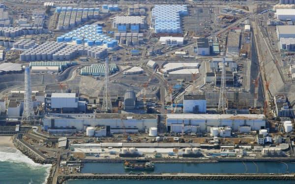 廃炉作業が続く福島第1原発の(右から)1号機、2号機、3号機、4号機。奥には汚染処理水などが入ったタンクが並ぶ(1日、福島県大熊町)