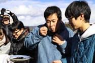 「ざざ虫」のつくだ煮を食べる今村大晴さん(右から2人目、長野県伊那市)=共同