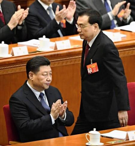 開幕した中国全人代で、政府活動報告のため席を立つ李克強首相。左は習近平国家主席=5日、北京の人民大会堂(共同)
