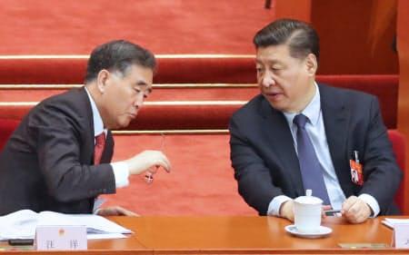 李首相が政府活動報告をするなか、汪洋政協主席(左)と言葉を交わす習主席(5日、北京の人民大会堂)=横沢太郎撮影