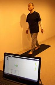 足底圧計測マットの上を歩く両備HDの小嶋会長。データはリアルタイムで表示される(5日、岡山市)