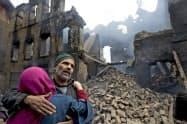 5日の砲撃戦でカシミール地方のインド支配地にある自宅を崩壊された男性ら=AP