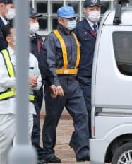 保釈され、作業員にふんした姿で軽自動車に乗り込む日産自動車のゴーン元会長(中央)=6日午後、東京都葛飾区の東京拘置所