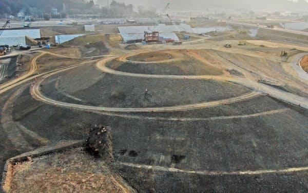震災復興祈念公園の整備が進む宮城県南三陸町。高さ約20メートルの「祈りの丘」が姿を現した。奥は旧防災対策庁舎(2日)