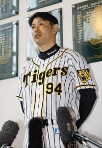 手術後初めてチームに合流し、ユニホーム姿で取材に応じるプロ野球阪神の原口文仁選手(7日午前、兵庫県西宮市)=共同
