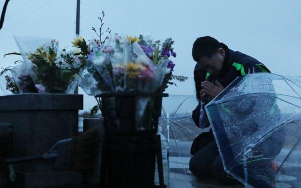 慰霊碑に手を合わせる人たち(11日午前、仙台市若林区)